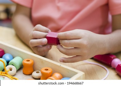 Little boy with Montessori material colored beads