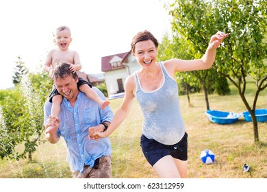 Little boy with mother and father at the sprinkler