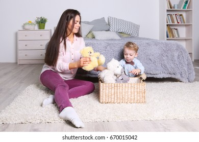 Little boy, mother play with toys in basket in cozy bedroom at home