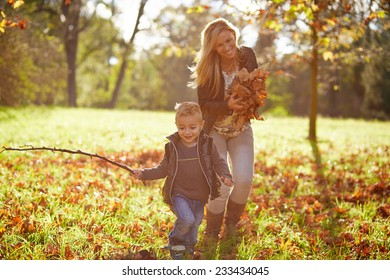 Little boy and mother playing together in the autumn park