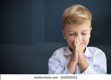 Little boy in namaste position meditating with eyes closed.