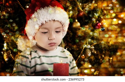 little boy near  a Christmas tree. boy blows out the candle