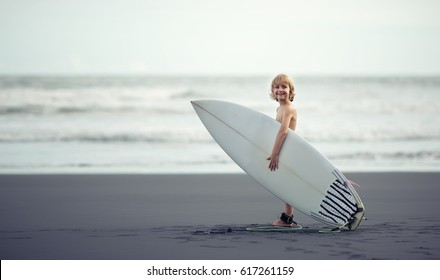 Little boy near the ocean with a surfboard smiling to camera