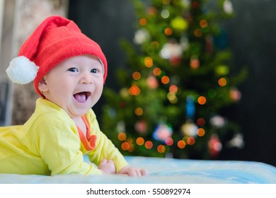 Little boy in a New Year's red hat is happy and smiles. Home comfort and warmth, and Christmas lights on a Christmas tree. Baby laughing and crawling on the bed