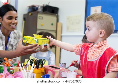 Little boy in nursery showing his teacher the cereal box car he has made.