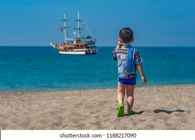 Little boy on a beach looking at a ship in the sea