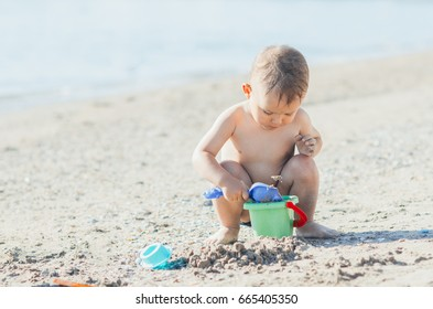 little boy on the beach near the sea playing, collecting sand pail shovel