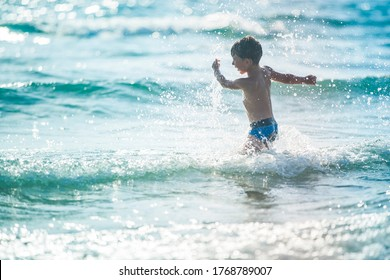 A little boy on the beach, playing with the waves, summer time. Concept of relaxation and a healthy lifestyle