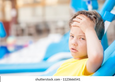 Little boy on the beach with a sunstroke touches his forehead, checking the temperature