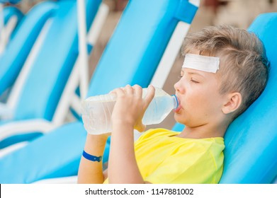 Little boy on the beach with a sunstroke drink water