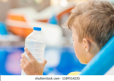 Little boy on the beach with a sunstroke holds a bottle of water