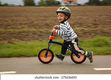 Kleiner Junge auf einem Fahrrad. Gefangen in Bewegung, auf einer Einfahrt (Bewegung unscharf). Der erste Tag der Vorschule auf dem Rad. Die Freude der Bewegung. Kleiner Athlet lernt, beim Fahrradfahren die Balance zu halten.