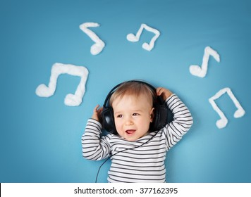 little boy on blue blanket background with headphones