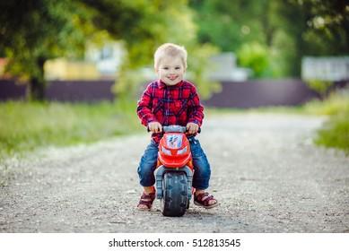 Little boy on a children's bike in the park