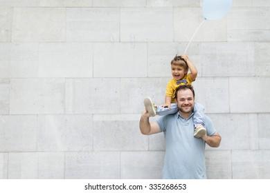 little boy on dad shoulders