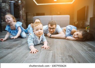Little boy on the floor, family in the background