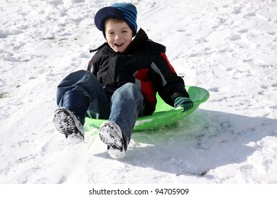 Little boy on his sled, enjoying winter