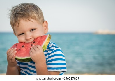Little boy on holiday eating watermelon