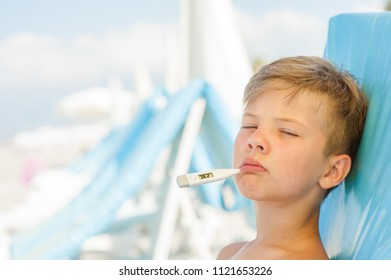 Little boy on hot beach with sunstroke measures the temperature. Space for text.
