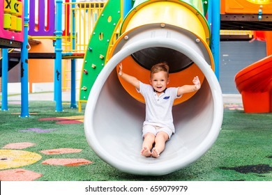 Little boy is on the playground pulls down the pipe down, summer, happiness, vacation