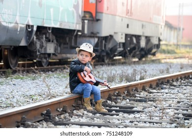 Little boy on railway station playing guitar. Child playing guitar