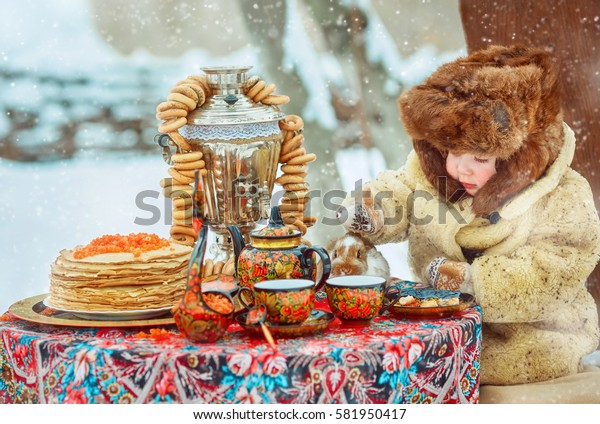 little boy on the street in a fur hat and coat. Retro National Russian flavor. Table decorated for the festivities. Pancake week. Feast of the end of winter
