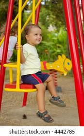 little boy on swings