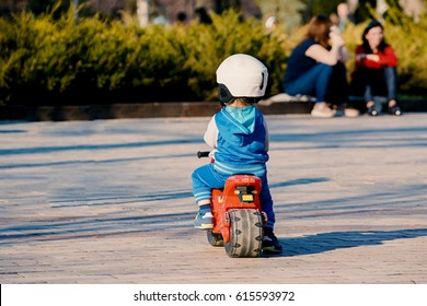 Little boy on a toy motorcycle