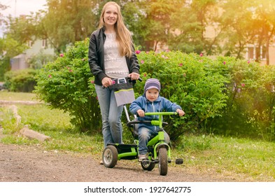 A little boy on a tricycle, a stroller with his mother.