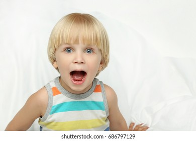 Little boy with open mouth sitting in white bed