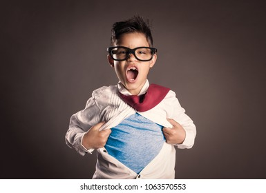 little boy opening her shirt like a superhero on a gray background