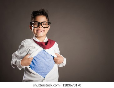 little boy opening his shirt like a superhero on a gray background