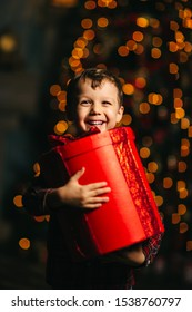 little boy opens gifts on the background of the Christmas tree