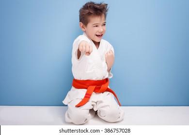 Little boy with orange belt on kimono. Karate.