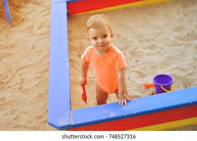 Little boy in orange clothes standing in the sandbox with his red shovel.
