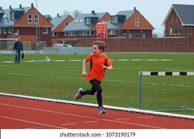 Little boy in orange outfit runs on the running track while he looks back at his competitors.
