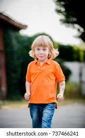 Little boy in an orange t-shit running on the street with his fists in air