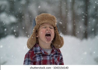 A little boy is outside catching snowflakes on his tongue in the wintertime. The boy is playing outside in the storm in a fluffy winter hat and a plaid shirt tasting the snow in his mouth. Wintertime