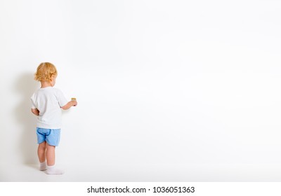 Little boy with paint brush standing back near white wall