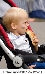 A little boy with a painted flag on his cheek. A child eats a croissant on the celebration Day of independence of Ukraine. Shooting on the street.