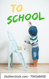 """A little boy is painting with paint on the wall. The inscription """"To School"""""""
