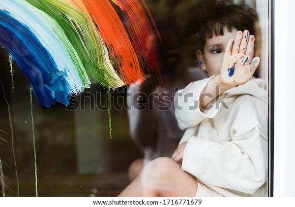 Niño pintando arco iris en una ventana y mirando por la ventana mientras se sienta en casa durante la cuarentena. Manos sucias. Estemos todos bien.