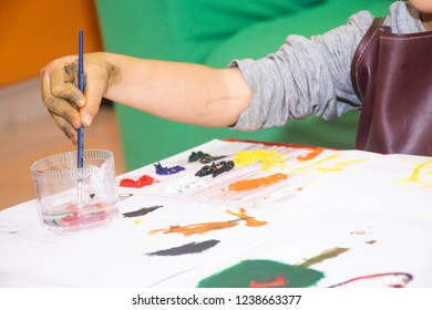 little boy painting sketchpad with a brush and water color paint, close up of his hands, child hoppy