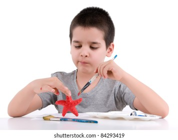 Little boy painting star fish over white background.