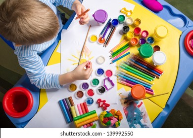 little boy painting at the table with art supplies, top view