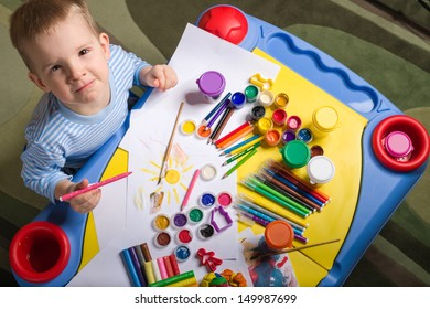 little boy painting at the table, top view
