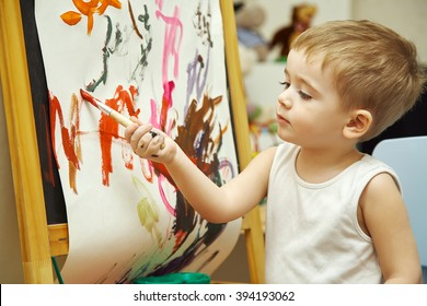 little boy paints a on an easel with a brush. painting child