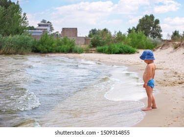 A little boy in a panama hat stands by the lake and looks at the waves.