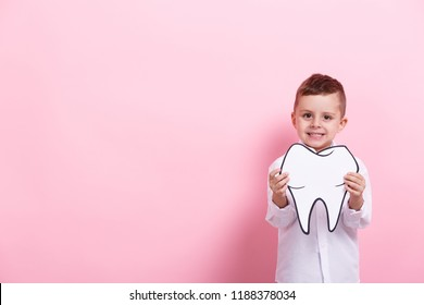 A little boy with a papercraft tooth on a pink background. Healthcare concept