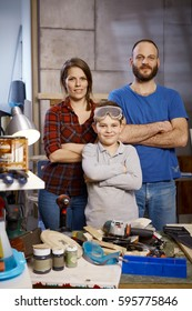 Little boy and parents standing arms crossed in workshop, looking at camera.
